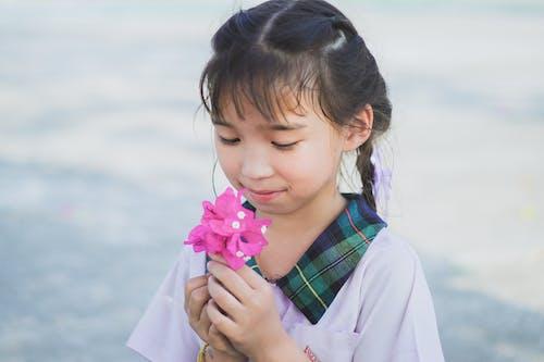 Girl in White Long Sleeve Shirt Holding Pink Flower