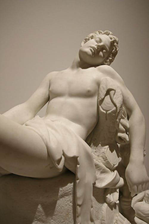 Classic stone sculpture of resting male