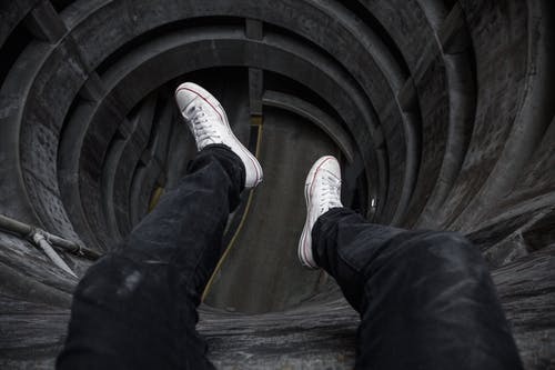 Person in Blue Denim Jeans and White Sneakers Standing on Tunnel