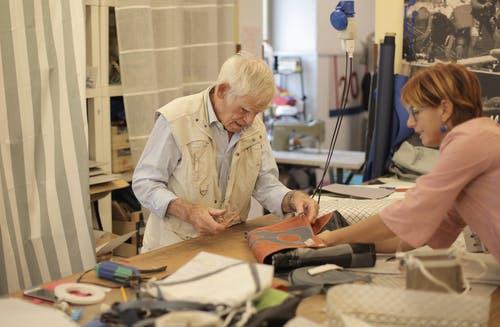 Aged craftsman making leather bag in workshop with assistant