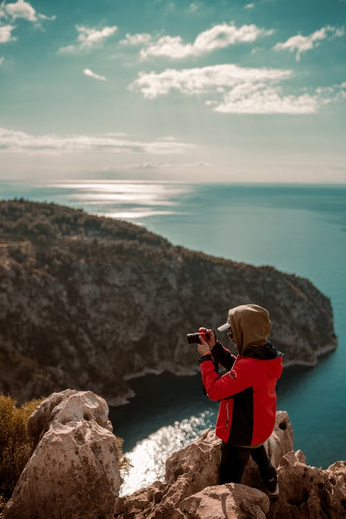 Woman in Red Jacket Taking Photo of Mountain