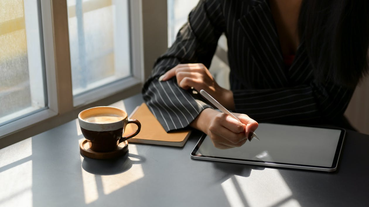 Person in Black and White Pinstripe Dress Shirt Using Tablet Computer