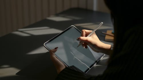 Person Holding White Ipad With White Case