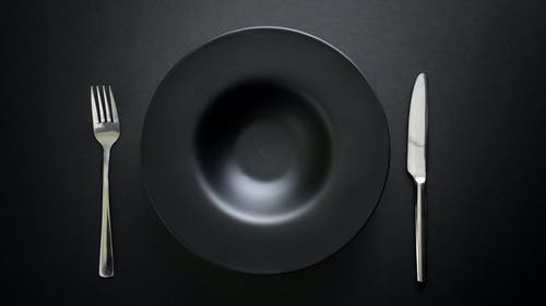 Photo of Black Plate Near Knife and Fork on Black Table