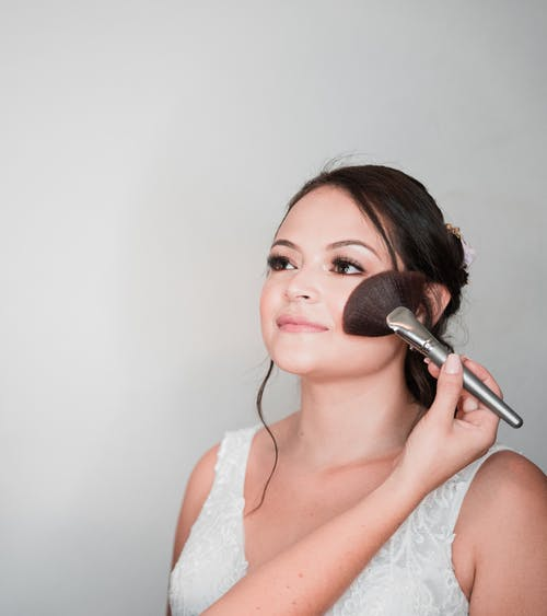 Charming bride during makeup session before wedding