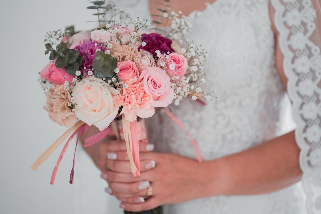 Woman in White Wedding Dress Holding Pink and White Rose Bouquet