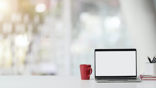 Photo of Laptop and Red Ceramic Mug on White Table