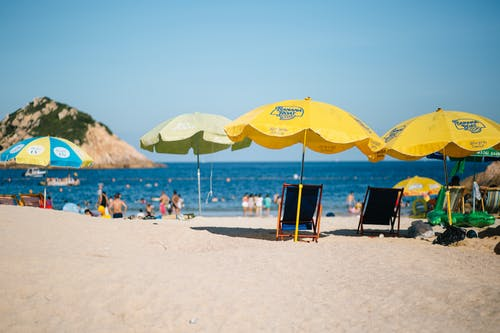 Photo of Folding Chairs and Umbrellas on Beach