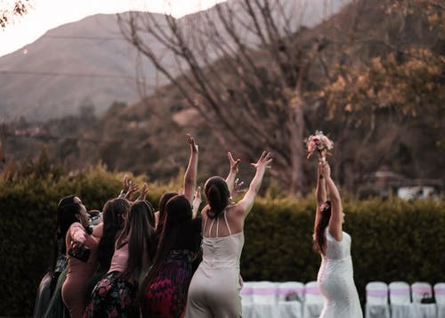 Woman throwing bouquet to bridesmaids