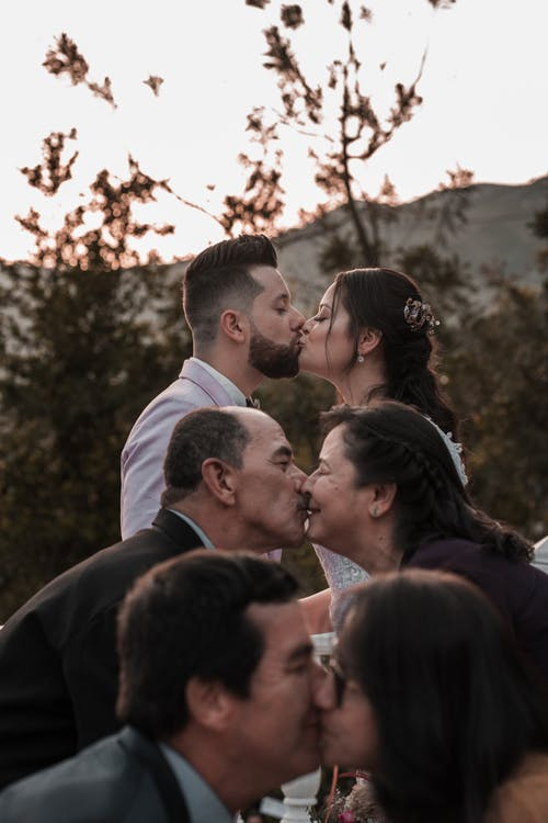 Elegant ethnic newlyweds and parents kissing on wedding day outdoors