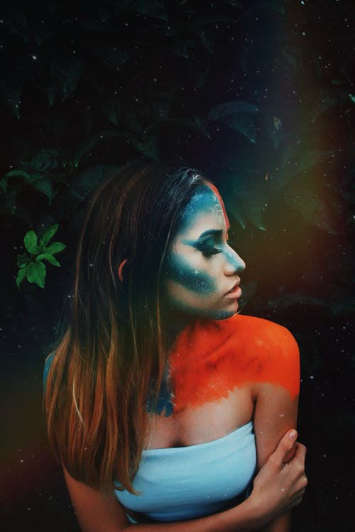 From above of young slim woman with blue paint on face and orange paint on shoulders representing cold and hot weather standing with closed eyes near tree branch with leaves