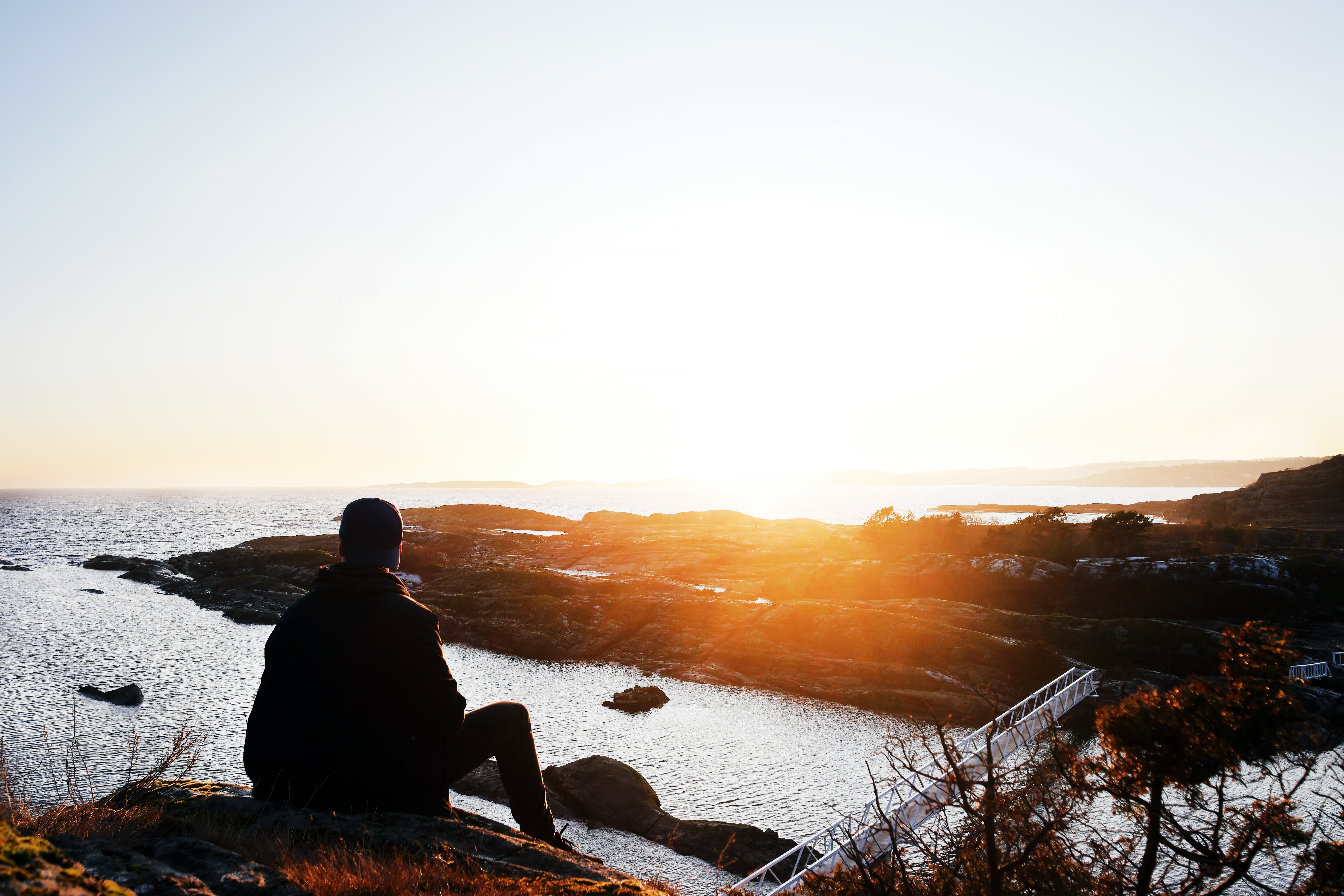 Silhouette Photo of Person Sitting Near Cliff during Golden Hour