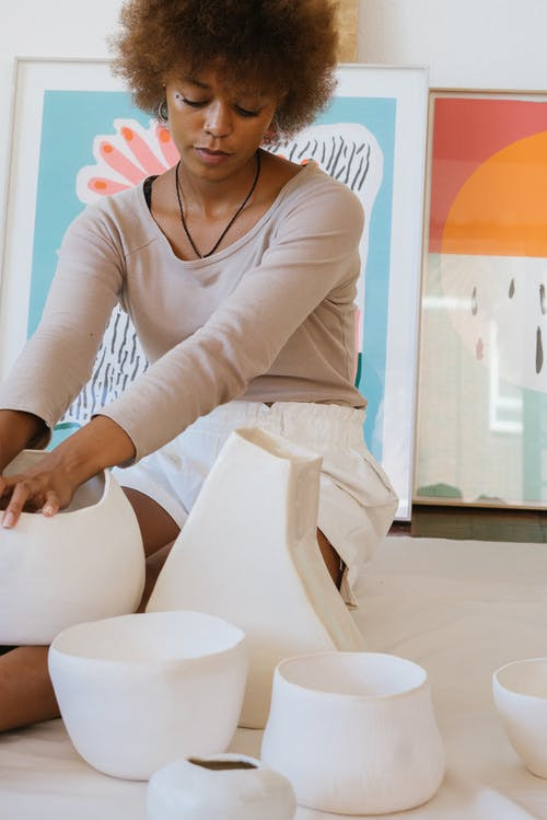 Talented black female artisan with ceramic pottery in workshop
