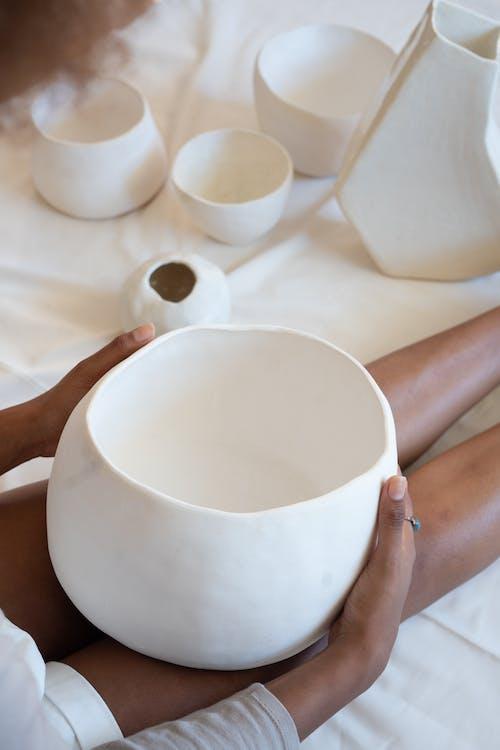 Black craftswoman with handmade ceramic bowl in workshop
