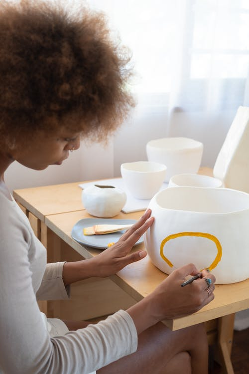 Skilled black craftswoman painting on ceramic earthenware in studio