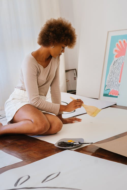 Photo of Woman Sitting on Floor While Holding a Paintbrush