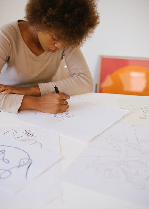 Photo of Woman Drawing on White Paper