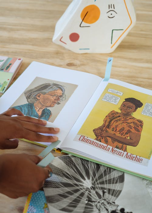 Ethnic female artist sticking bookmarks on pages