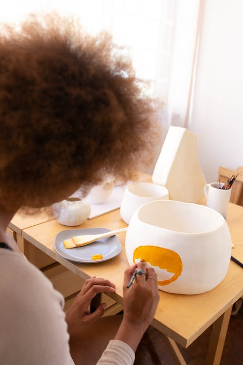 Creative black craftswoman paining picture on handmade pottery