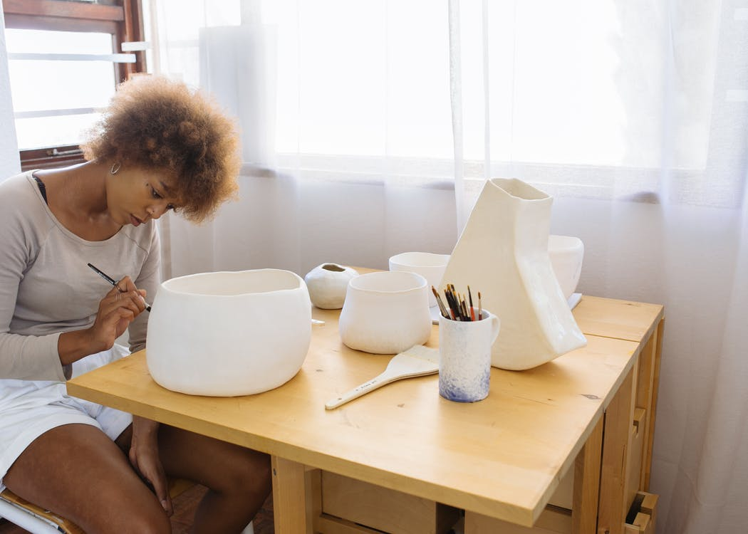 Focused young artist painting ceramic bowl