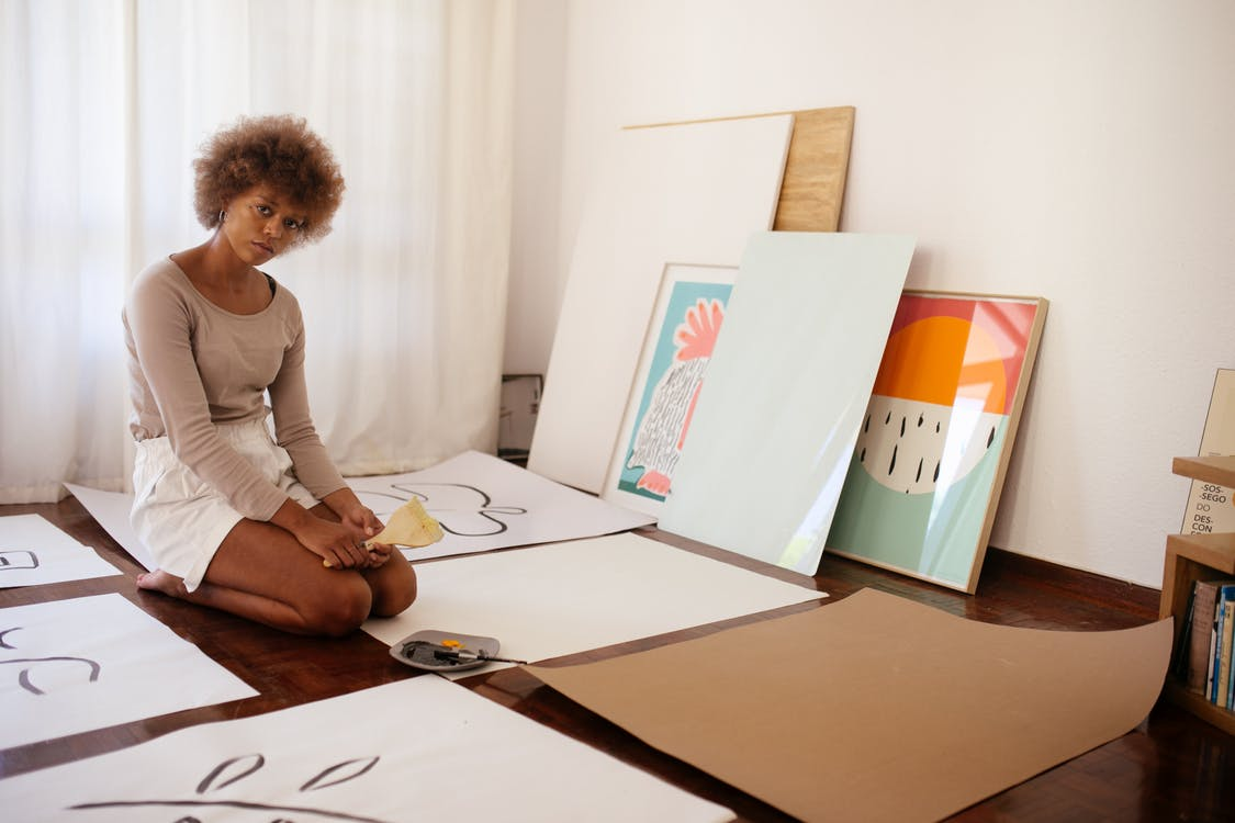 Young artist sitting on floor with artworks