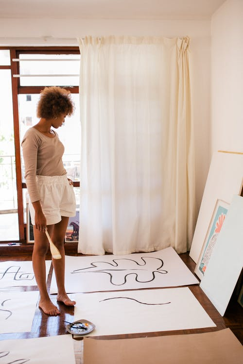 Side view of black barefoot female in casual outfit standing at cozy workspace and looking at colorful illustration by wall and abstract paintings on floor