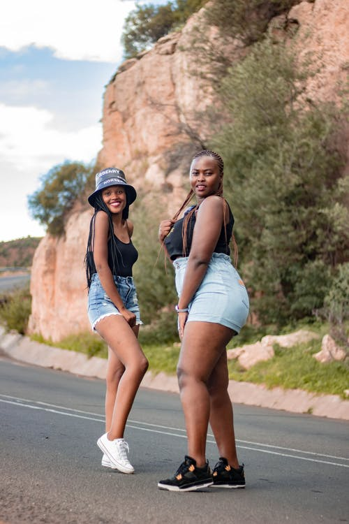 Photo of Women Smiling While Standing on Road