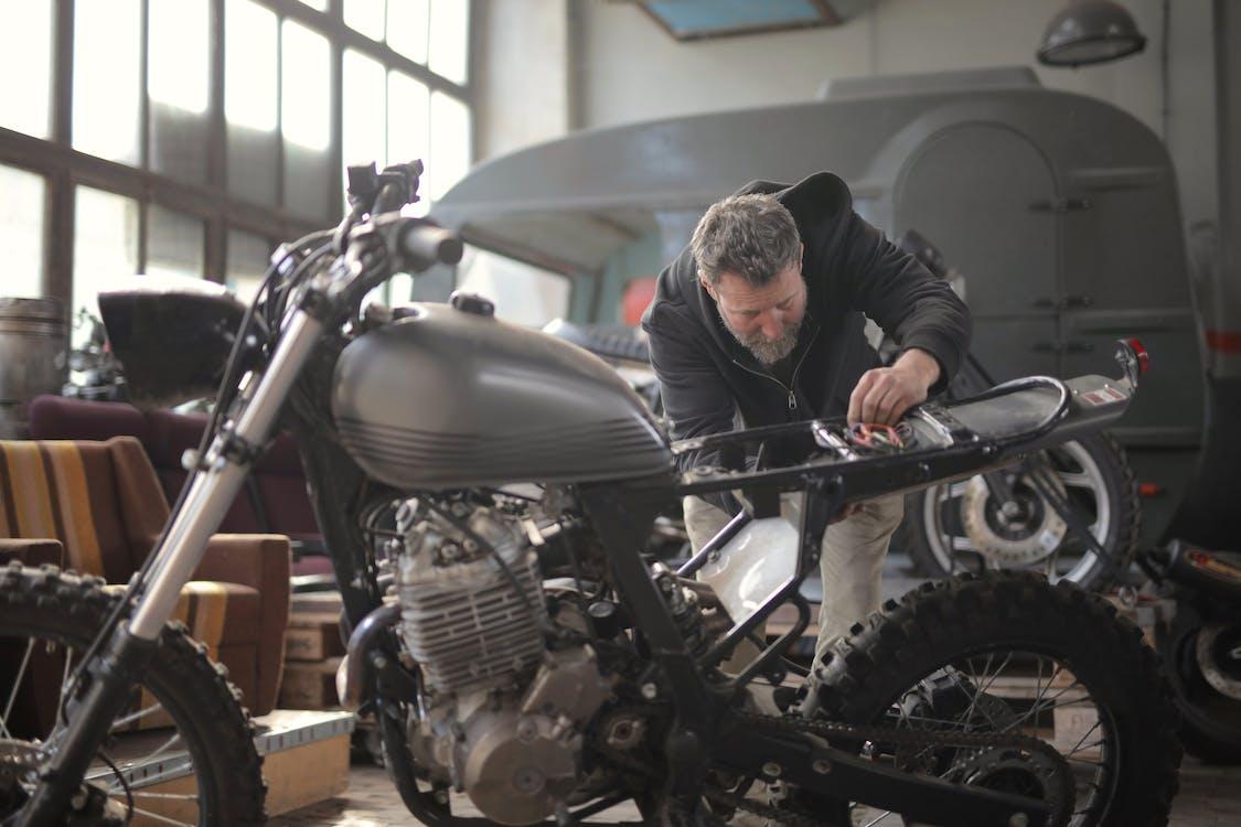 Man in Black Jacket Standing Near Black Motorcycle