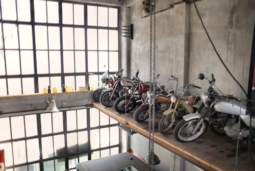 Retro motorbikes parked in row on special platform in garage
