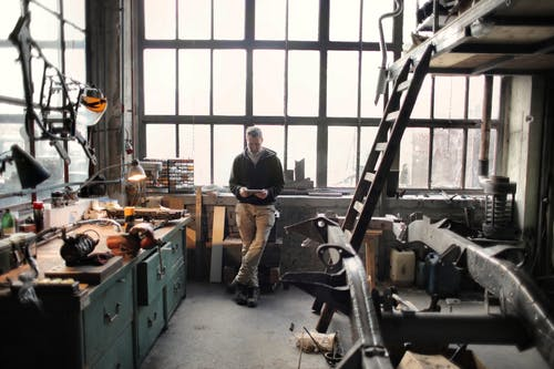 Photo of Man Standing Inside His Workshop