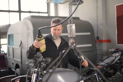 Male mechanic using hydraulic crane in garage