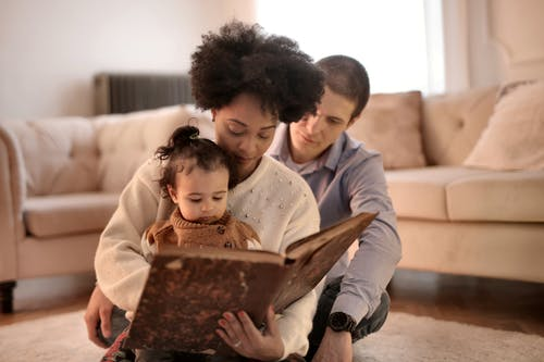 Photo of Woman Holding Brown Book With Her Child