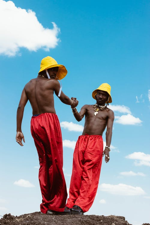Photo of Two Men Supporting Each Other Under Blue Sky