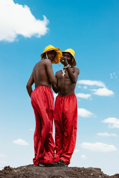 Men Wearing Red Pants and Yellow Hats