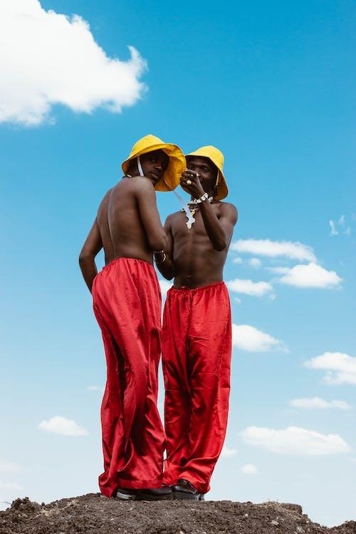 Hommes Portant Des Pantalons Rouges Et Des Chapeaux Jaunes