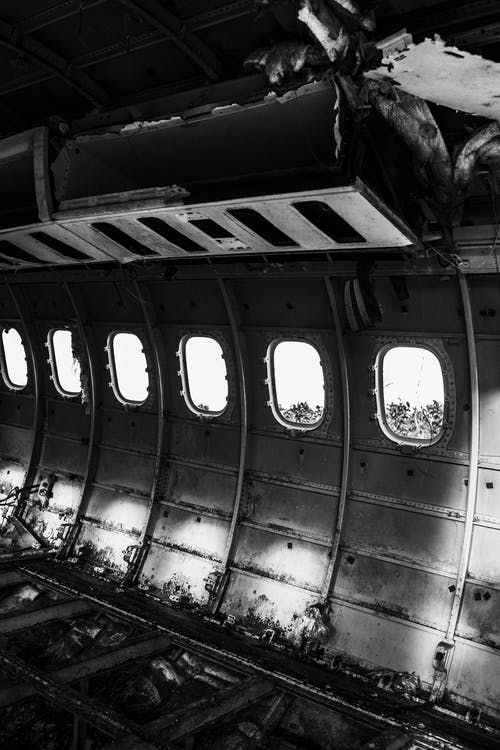 Interior of gray aged plane cabin with similar rounded windows and damaged metal rack and dirty surface after having accident