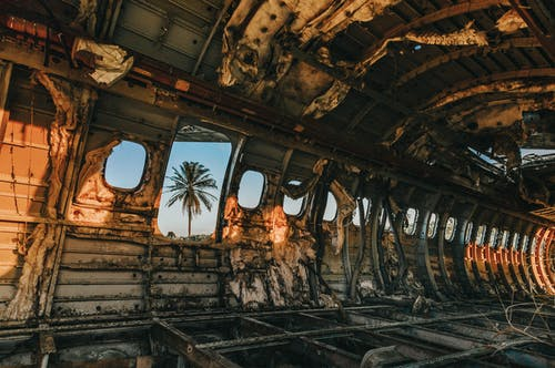 Damaged aircraft cabin interior at colorful sunset