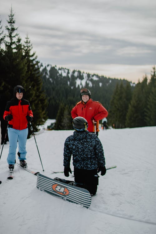 2 Men in Red Jacket and Black Pants Riding on Ski Blades on Snow Covered Ground