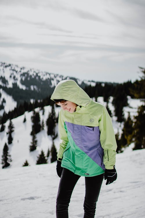 Person in Green Hoodie and Black Pants Standing on Snow Covered Ground