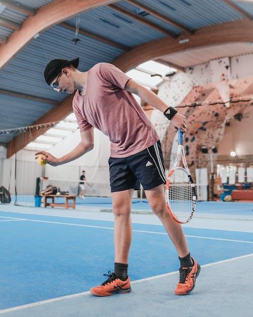 Mann Im Roten T Shirt Und In Den Schwarzen Shorts, Die Tennis Spielen