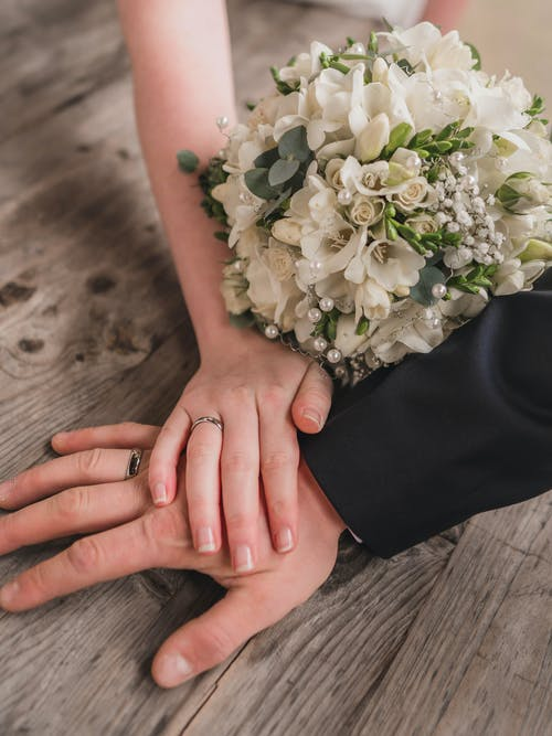 Photo of Hands With Wedding Rings and Bridal Bouquet