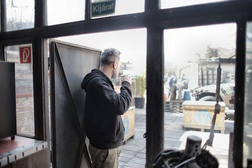 Man in Black Jacket Standing in Doorway