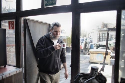 ガラスのドアの横に立っている黒いジャケットと茶色のズボンの男
