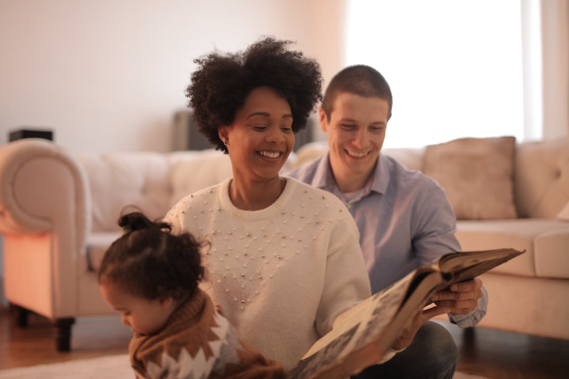 Photo of Man and Woman Smiling While Holding a Book