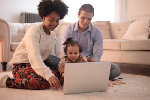 家人在使用筆記本電腦時坐在地板上的照片