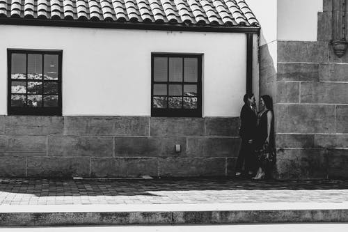 Photo of Couple Standing by the Concrete Building