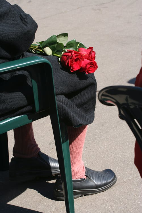 Person in Black Clothing and Red Socks Sitting on Green Plastic Chair