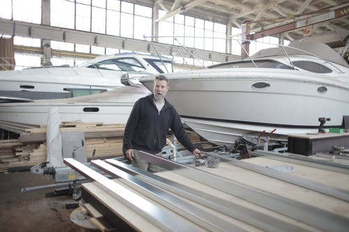 Male master in hangar with motor boats