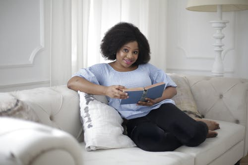 Woman in Blue Shirt and Black Pants Sitting on White Couch