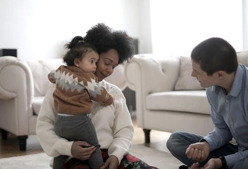 Toddler hugging black mother at home